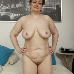Old saggy granny happily poses nude and spreads her legs