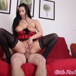 Curvy wife in a red corset and black stockings gets penetrated on her new couch